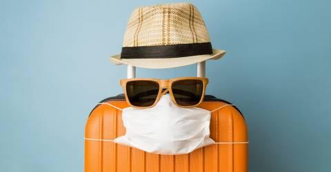 Koffer met hoed, zonnebril en beschermend medisch masker op blauwe achtergrond